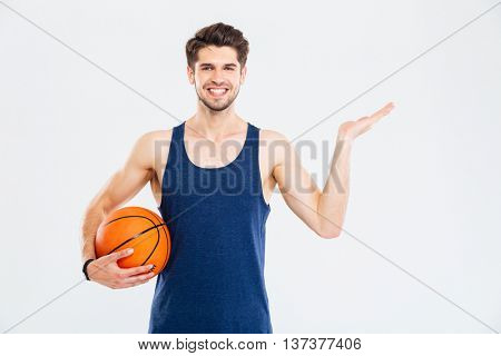 Cheerul young sportsman with basketball ball holding copyspace on palm over white background