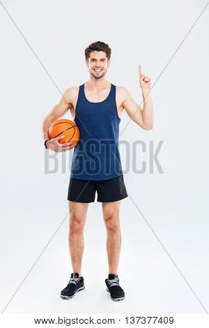 Smiling young sportsman holding basket ball and pointing finger up at copyspace isolated on a gray background