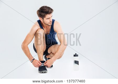 Closeup of man athlete with bottle of water tie shoelaces on his sneakers over white background