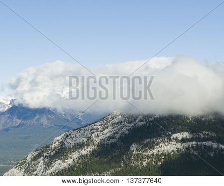 Taken in Banff, Alberta, this image was taken on a hike to the top of Sulfur Mountain. A little cloud coverage loomed over a top of a peak, creating shadows.