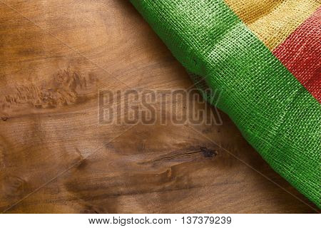 Wooden background with flag of Benin. National colors of the flag of Benin.