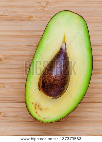 Fresh Avocado On Wooden Background. Organic Avocado Healthy Food Concept. Avocado On Bamboo Cutting