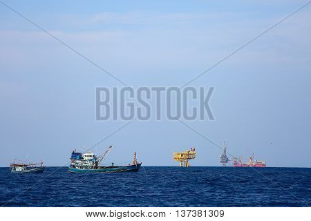 Fishing boat operation in the gulf for find fresh fish, Worker fishing the fish with team each day and night time, Fishermen working with supply boat for transfer fresh fish back to onshore for sale.