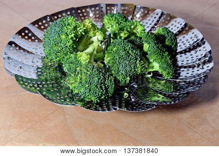 Fresh Brocolli florets in a steamer strainer