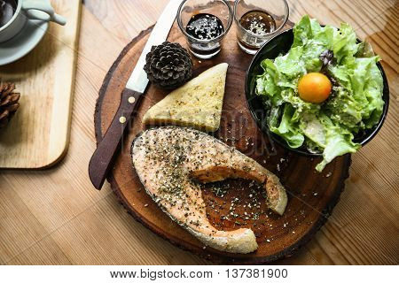 Salmon steak on wooden table in restaurant, Fresh steak for healthy food and clean food or fresh food for diet, International steak on plate with fresh vegetable or salad in the restaurant.