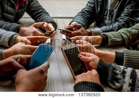 group of multi-racial people using smart phones at the table close up crop on hands
