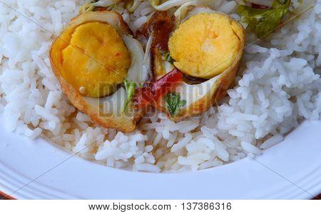 fried egg with sweet tamarind sauce half cut on rice