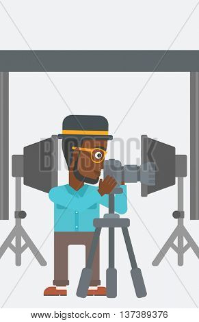 An african-american photographer working with camera on the background of photo studio with lighting equipment vector flat design illustration. Vertical layout.