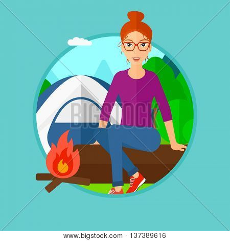 Woman sitting on a log near a fire on a background of camping site with tent. Young woman sitting near a campfire at a campsite. Vector flat design illustration in the circle isolated on background.