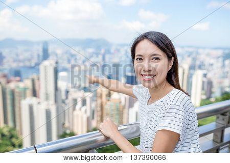 Woman traveler pointing to city of Hong Kong