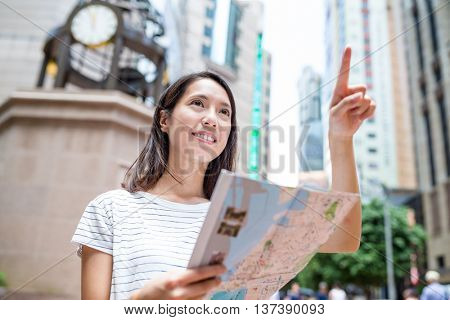 Asian woman holding city map and finger pointing up
