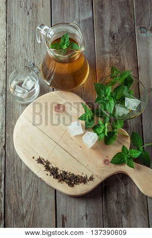 Green tea and mint on a cutting board. In the background a pitcher