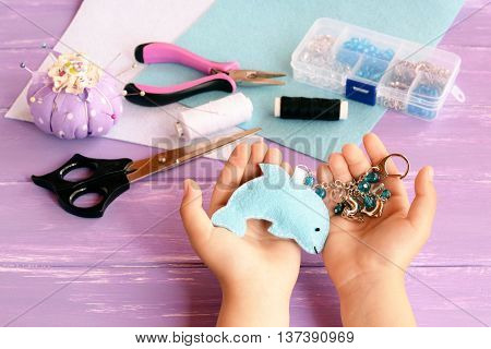 Child holds a felt dolphin toy in his hands. Home blue felt keychain with beads. Pincushion, thread, needles, pins, scissors, pliers, felt sheets, box of beads. Children sewing crafts concept