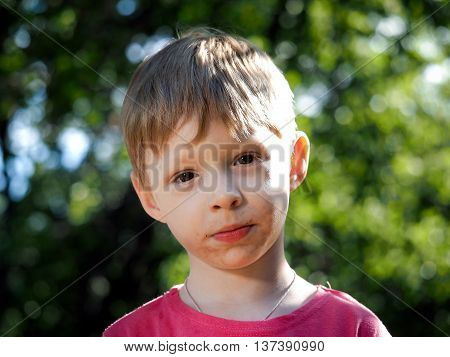 Portrait of a little boy. A child in the street summer heat sun rays. On the face of dirt grimy and happy child Russian