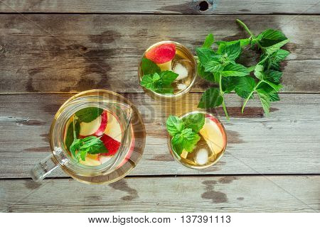 Two glass and carafe of green tea with mint and apples flat lay