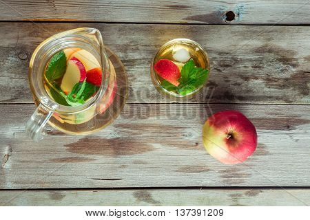 Glass and carafe of green tea with mint and apples flat lay