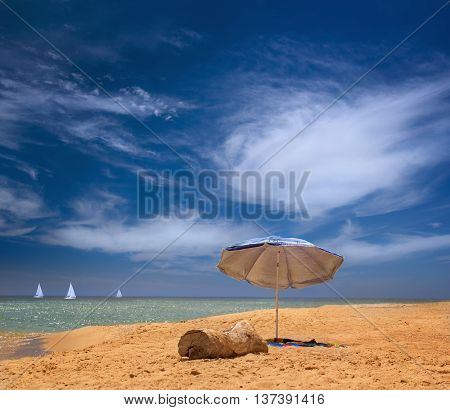 An installed beach umbrella at the beach of the Black Sea over beautiful sea scape with yachts in Odessa region in Ukraine