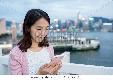 Woman texting ong cellphone in Hong Kong