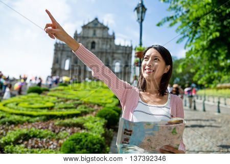 Woman holding city map and finger pointing far away