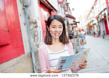 Woman looking at city map in Macau city