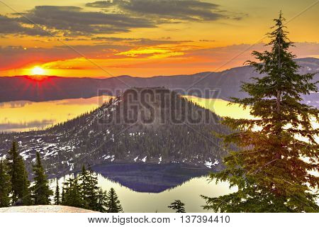 Sunrise at Crater Lake with red clouds reflection in lake.