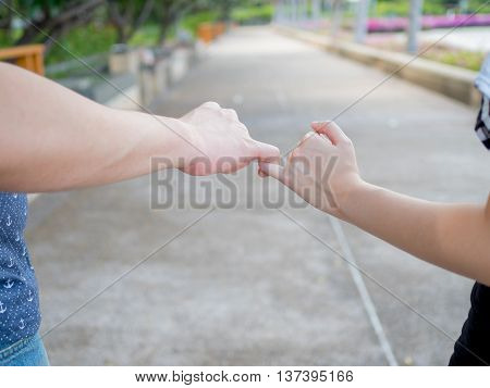 Man And Woman In Relationship Crossing Pinky Finger As Promised