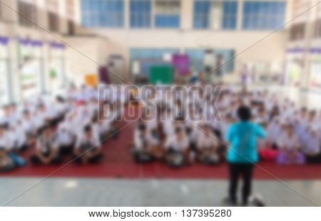 Blurred abstract background of university students sitting in a lecture room with teacherTeachers day.