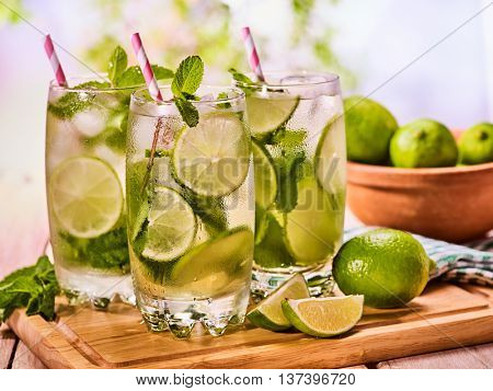 Alcohol drink. On wooden boards three glasses with alcohol drink and ice cubes. A drink number forty five cocktail mohito with straw and lime and mint leaf. Country life. Outdoor. Light background.
