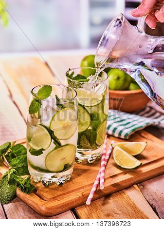 Country drink. Hand is pouring from jug of cocktail drink on wooden boards with lime and mint . Drink number forty with mohito cocktail and ice cubes . Country life. Light background.