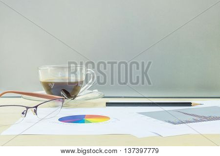 Closeup black coffee in transparent cup of coffee with work paper and pencil and eyeglasses on blurred wooden desk and frosted glass wall textured background work concept by coffee and work paper