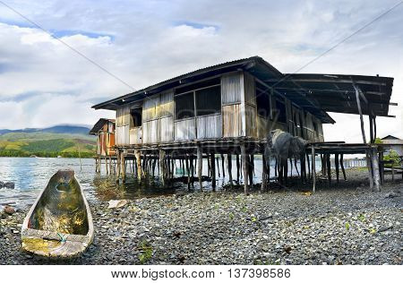 Boat And Cottage On Piles Ashore Lake Sentani