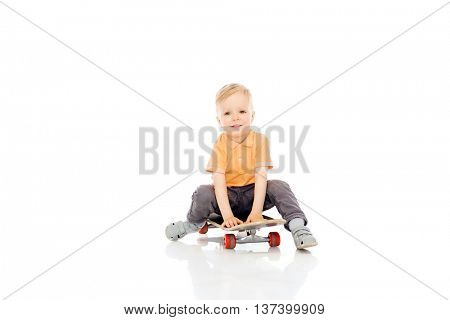 childhood, sport, leisure and people concept - happy little boy sitting on skateboard