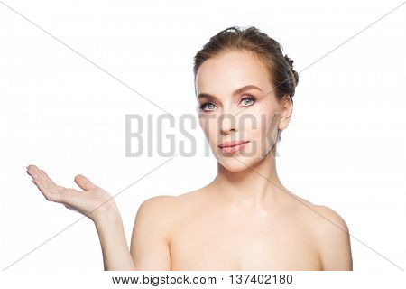 beauty, people, advertisement and health concept - smiling young woman holding something on palm of her hand