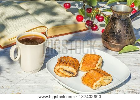 Breakfast with coffee and pastries in the garden under the cherry tree in the sunny summer morning