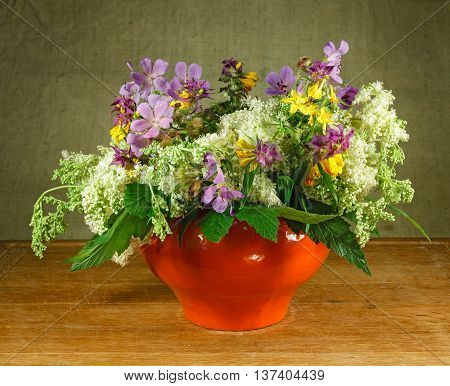 Still life. Bouquet of meadow flowers in orange pots standing on a wooden table. Rustic style. Meadow geranium meadowsweet hypericum perforatum melampyrum nemorosum .