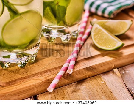 Alcohol drink. On wooden boards part of two glasses with alcohol drink and ice cubes. A drink number forty two cocktail mohito with straw and lime and mint leaf. Country life. Light background.