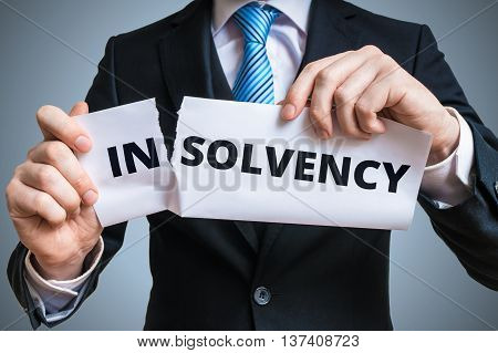 Debt relief concept. Businessman is tearing paper with insolvency word to make solvency word.