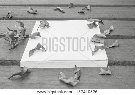 Closeup note book on wooden table in the garden with dried leaves textured background in black and white tone