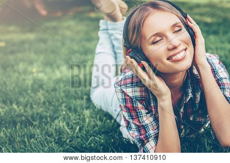 Enjoying music in nature. Beautiful young woman in headphones listening to the music and smiling while lying on the green grass