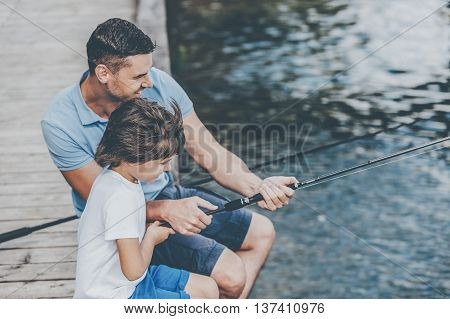 Father and son fishing. Top view of happy father and son fishing while sitting on riverbank