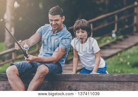 It is a big fish! Happy father and son fishing together and smiling while sitting on quayside