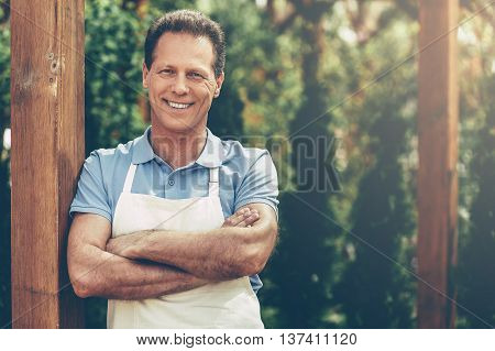 Confident gardener. Handsome mature man in apron keeping arms crossed and looking at camera while standing in a greenhouse