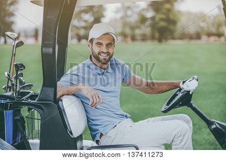 On the way to next hole. Side view of young happy male golfer driving a golf cart and looking at camera