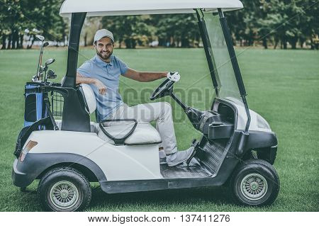 Driving golf cart. Side view of handsome young man driving a golf cart and looking at camera