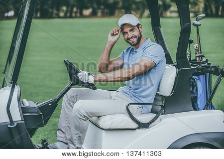 Man in golf cart. Side view of handsome young man driving a golf cart and looking at camera