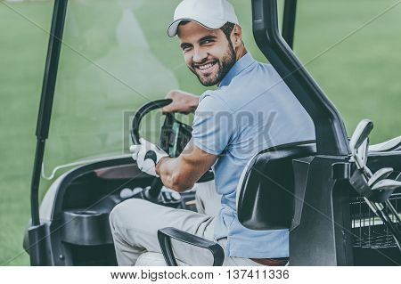 On the way to next hole. Rear view of young happy male golfer driving a golf cart and looking over shoulder