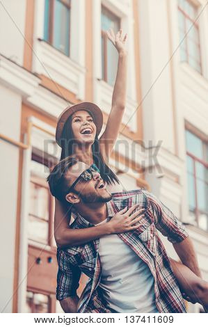 Carefree fun. Happy young man carrying his beautiful girlfriend on shoulders and smiling while walking by the street
