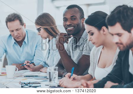 Happy to be a part of grat team. Group of business people sitting in a row at the table while handsome African man looking at camera and smiling