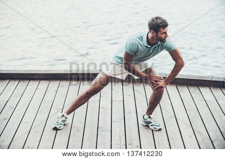 Exercising on fresh air. Confident young man doing stretching exercises while standing on quayside