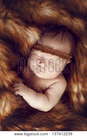 newborn baby sleeping peacefully on the red fur warmed by the fur of a Fox